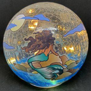 mermaid gazing globe and light